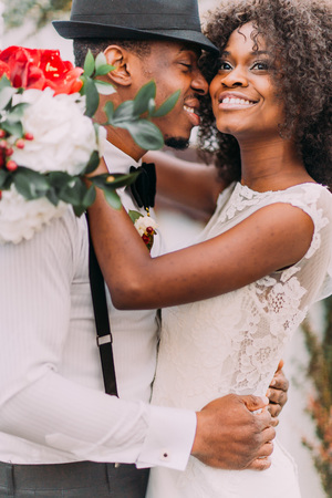 Charming african bride and stylish groom in black hat happily laughing and smiling close up. Wedding day. Standard-Bild