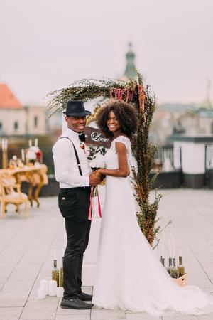 Heureux couple de mariage africain souriant et tenant les mains sur le toit.