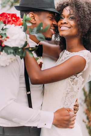 Beautiful african bride and happy groonm in black hat  embracing on the weddig ceremont close up.