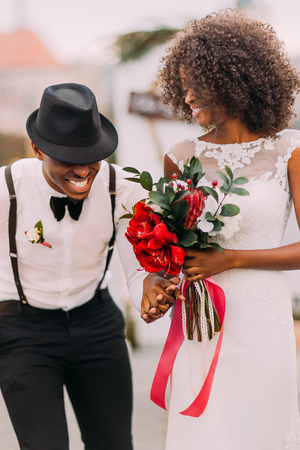 black woman white man: Stylish black groom in hat and his charming bride happily laughing on their wedding ceremony.