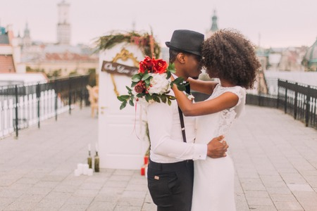 softly: Happy black wedding couple softly hugging on the rooftop during the wedding ceremony. Stock Photo