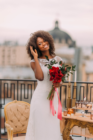 corrects: Happy black bride corrects her hair and smiling. Wedding day.
