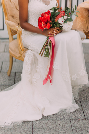 sits on a chair: African bride with wedding bouquet in hands sits on vintage terracotta chair in half-length.