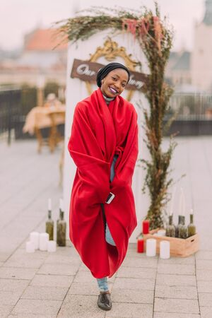 red plaid: Stylish black girl  in red plaid cheerfully smiling on the rooftop.