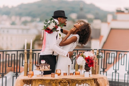 Stylish african wedding couple having fun on the balcony with luxury golden table in oriental style on foreground.