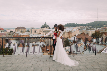 adoring: Happy black wedding couple softly hugging on the rooftop. Stock Photo