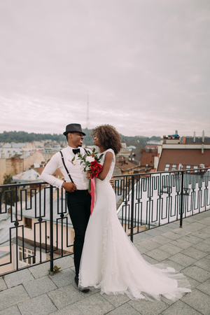 lovingly: Beautiful african wedding couple lovingly look at each other on the rooftop. Stock Photo