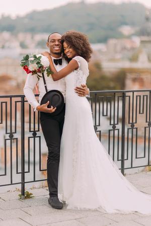 Felice sposa in bianco e lo sposo dolcemente abbracciano sulla terrazza con la città a sfondo.