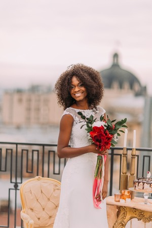 Happy curly black bride on the rooftop smiling. Wedding day.