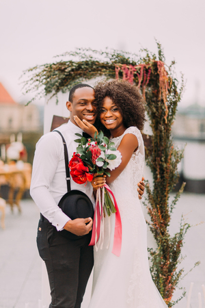 Happy black newlyweds smiling and hugging on the rooftop during their wedding ceremony. Banco de Imagens