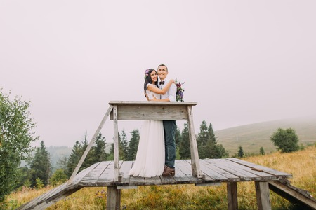 a meeting with a view to marriage: Beautiful wedding couple posing on the wooden bridge. Honeymoon in mountains. Stock Photo