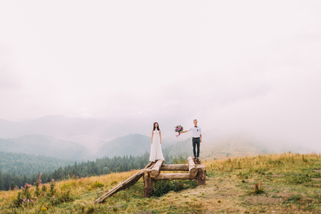 a meeting with a view to marriage: Wedding couple on the wooden bride. Misty day in the mountains. Stock Photo
