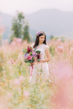 Beautiful bride with flowers on the field. Mountains on background. Banque d'images