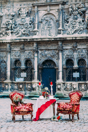 baroque architecture: Dreamlike red and white colored table with luxurious armchairs with the old baroque architecture on background. Stock Photo