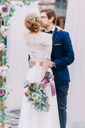 tenderly: Gorgeous wedding couple tenderly kissing (back view). Stock Photo