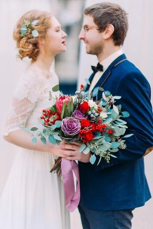 Jeune mariée magnifique avec bouquet de mariage vintage et élégant marié en caressant du regard de l'autre.