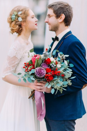 lovingly: Young gorgeous bride with vintage wedding bouquet and stylish groom lovingly looking at each other.