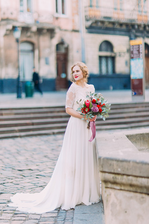 gracefully: Charming blond bride cheerfully smiling with bouquet in hands and ancient Lviv architecture on background.