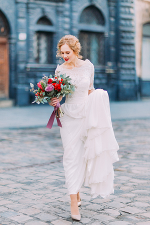 gracefully: Pretty bride with curly blond hair gracefully walks on streets of ancient european city.