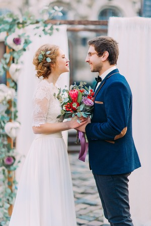 lovingly: Charming wedding couple lovingly looking on each other on the wedding ceremony. Stock Photo