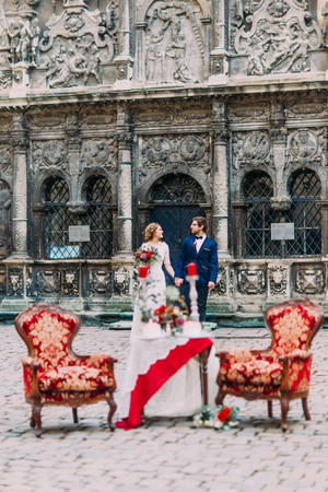 lovingly: Happy newlyweds holding hands and lovingly looking on each other with luxury vintage table and red armchairs on foreground Stock Photo