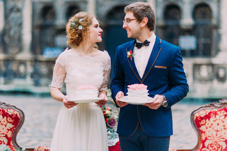 lovingly: Happy wedding couple lovingly look at each other with pieces of wedding cakes in hands. Stock Photo