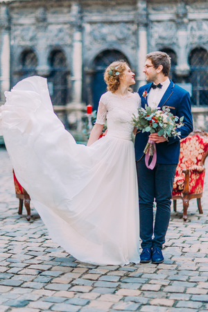 baroque architecture: Happy cheerful wedding couple happily smiling with old baroque architecture on background. Stock Photo
