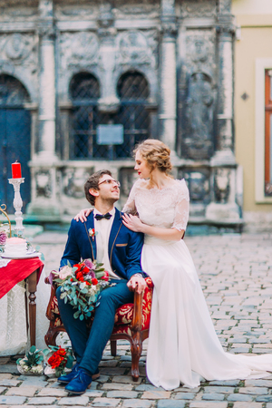 tenderly: Handsome groom and bride tenderly look on each other. Beautiful old Lviv architecture on background