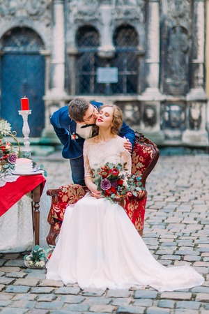 softly: Groom softly kisses his aristocratic blond bride sitting on red vintage armchair, Stock Photo