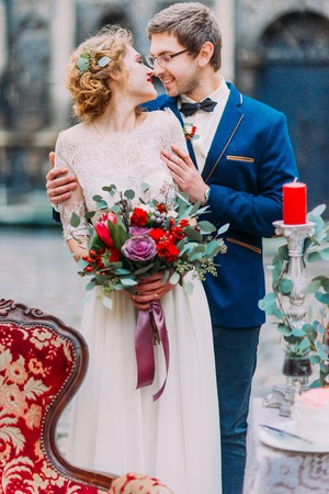 baroque architecture: Groom holds his fragile blonde bride on their wedding day with the old baroque architecture on background.