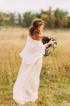 ethnic dress: Charming curly bride in ethnic dress on the field Stock Photo