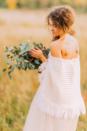 ethnic dress: Lovely tattoo bride in white ethnic dress with bouquet in hands on the autumn field.