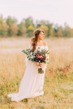 Charming curly bride in white ethnic dress and bouquet on the autumn meadow.