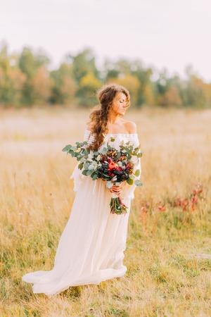 Mariée bouclés Charme en robe ethnique blanc et bouquet sur la prairie d'automne. Banque d'images - 53609603