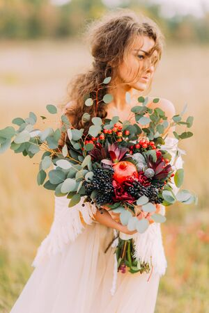 nuptials: Charming curly bride with autumn fruits in hands standing on the autumn meadow. Stock Photo