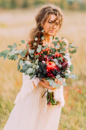 softly: Lovely bride in white ethnic dress holds bouquet  and softly smiling .