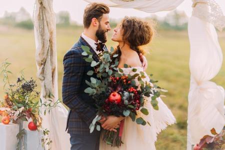 Heureux couple de mariage avec amour regarder l'autre lors de la cérémonie sur la prairie. Banque d'images - 53609622