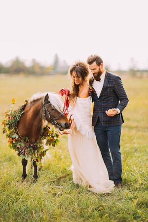 Happy wedding couple feeding pony on the field.