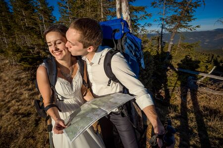 honeymoon: Wedding tourist couple with map kissing. Honeymoon in the mountains.