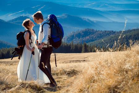 tourist wedding couple hugs on the top of the mountain. Honeymoon in Alps.