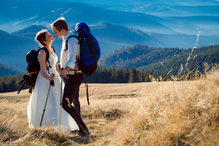 tourist wedding couple hugs on the top of the mountain. Honeymoon in Alps. Stok Fotoğraf - 53609445