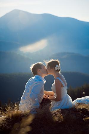 tenderly: Romantic wedding couple tenderly kiss. Wonderful Alps on background.