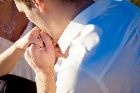 tenderly: Groom tenderly kisses brides hand close up.