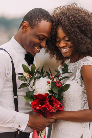 African wedding couple softly smiling with bouquet in hands.