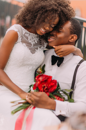 lovingly: African wedding couple lovingly hugging with bouquet of red flowes. Stock Photo