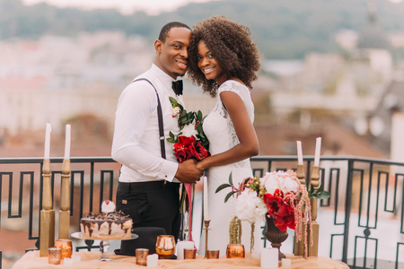 Goregous black wedding couple happily smiling and holding hands.