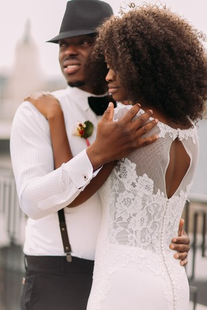 Happy stylish african groom in hat and suspenders holding his pretty african bride.