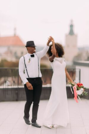 gracefully: Happy newly wed black couple gracefully dances on the rooftop. Wedding day.