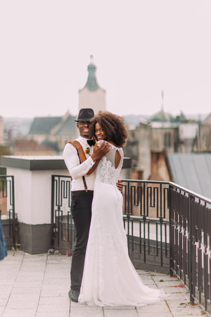 Charming african wedding couple hugging on the terrace with amazing view on old Lviv city architecture. Banco de Imagens