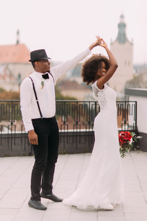 African wedding couple gracefully dancing on the rooftop.